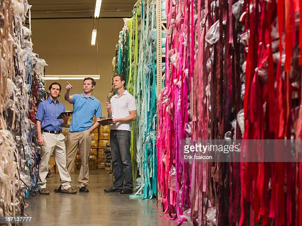 Workers examining fabric in textile factory