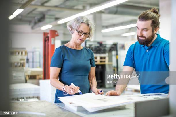 workers examining printouts at printing plant - printing press stock pictures, royalty-free photos & images