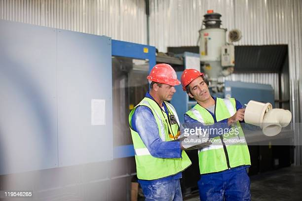 Workers examining product in factory