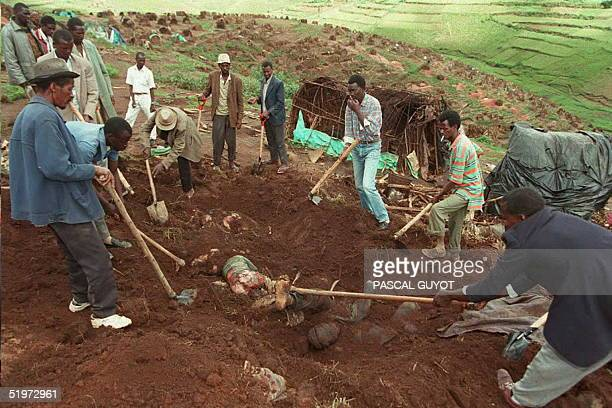 Workers exhume bodies from a mass grave at the Kibeho refugee camp 27 April to count the dead following the massacre of Hutu refugees allegedly...
