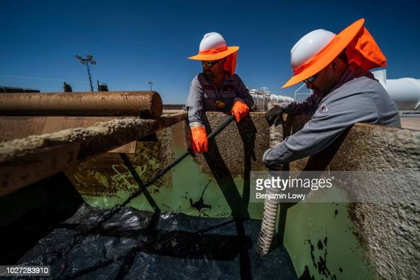 Workers extracting oil from oil wells in the Permian Basin in Midland Texas on May 5 2018 Oil production has been causing a sudden influx of money...