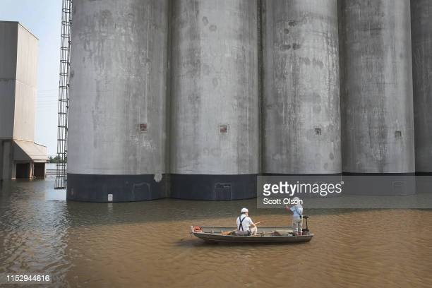 Workers ferry supplies through floodwater from the Mississippi River across Highway 100 to Ardent Mills on May 31 2019 in Alton Illinois The...