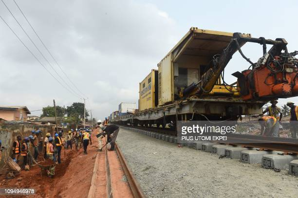 Workers fill a section of the new standard gauge railway line under construction from Iju in Lagos to Abeokuta, Ogun State in southwest Nigeria, on...