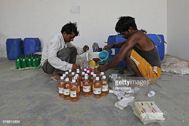 Workers fill bottles of cow urine at a processing facility in Greater Noida Uttar Pradesh India on Friday June 17 2016 Urine from India's indigenous...