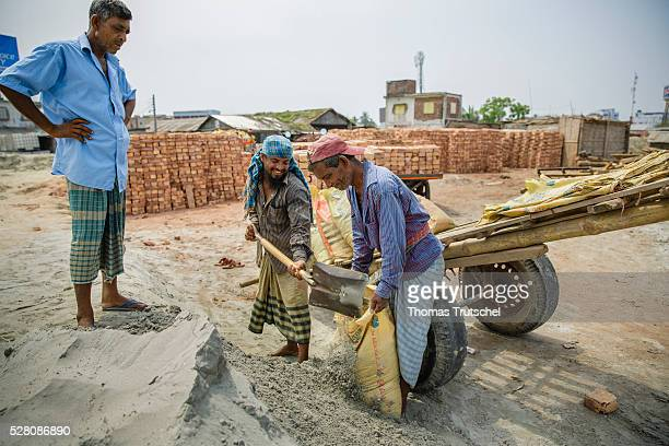 Workers fill sand into bags on a construction site on April 12 2016 in Mongla Bangladesh
