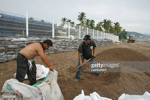 Workers fill sandbags on the beach as they protect the Pan American Beach Volleyball Stadium, still under construction, before the arrival of the...
