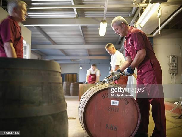 Workers filling whisky barrels in distillery