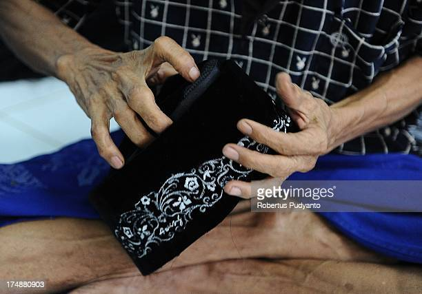 Workers finish attaching the lining of skull caps at Awing traditional Muslim skull cap manufacturers on July 29 2013 in Gresik Java Indonesia Awing...