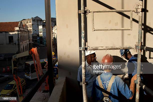 Workers finish construction details on the Gamboa cable car station in Rio de Janeiro, Brazil, on Tuesday, April 16, 2013. Scheduled to open to the...