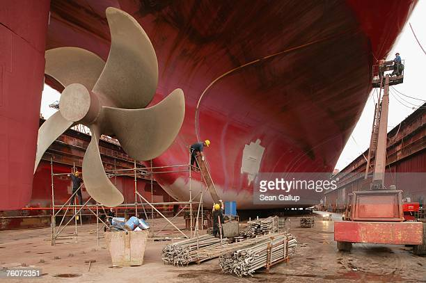 Workers finish maintenance work on a cargo ship's propeller as other workers paint its hull during repairs of the ship at the Blohm Voss shipyard...