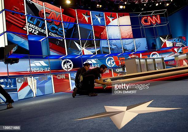 Workers finish preparing the debate hall before the Republican presidential candidates' debate on February 22 2012 in Mesa Arizona The candidates...