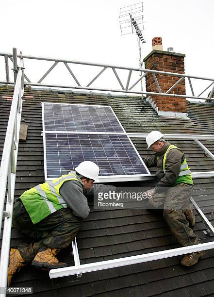 Workers fit solar panels to a roof of a council house in Wrexham Wales on Friday Feb 24 2012 UK house prices held their value for a second month in...