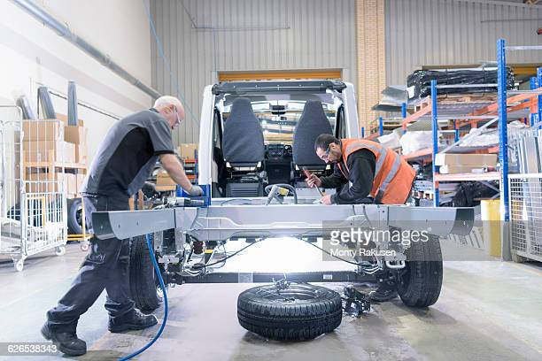 workers fitting chassis on motorhome production line - chassis stock pictures, royalty-free photos & images
