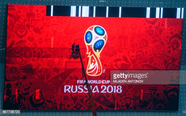 TOPSHOT Workers fix a giant screen featuring the Russian FIFA World Cup logo mounted outside Rostov Arena in the southern Russian city of RostovonDon...