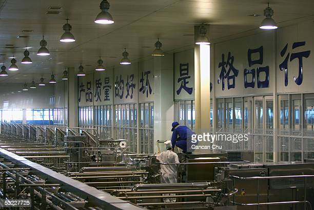 Workers fix a machine at a workshop at Mengniu Dairy Co Ltd's modern dairy farm July 12 2005 in Hohhot Inner Mongolia autonomous region in north...