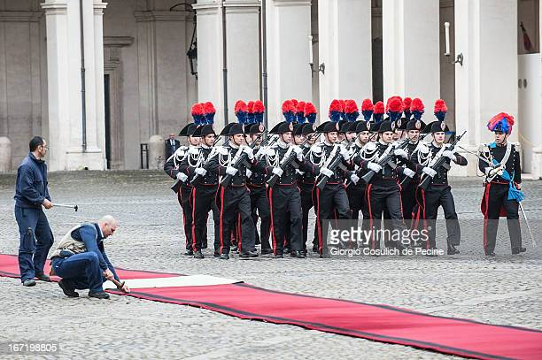 Workers fix a red carpet in front of the guard of honor as they wait the arrival of the newly elected President Giorgio Napolitano at Palazzo del...