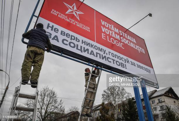 Workers fix an election campaign billboard of the Socialist Party reading We vote the star we vote the socialists It is logical in Chisinau on...