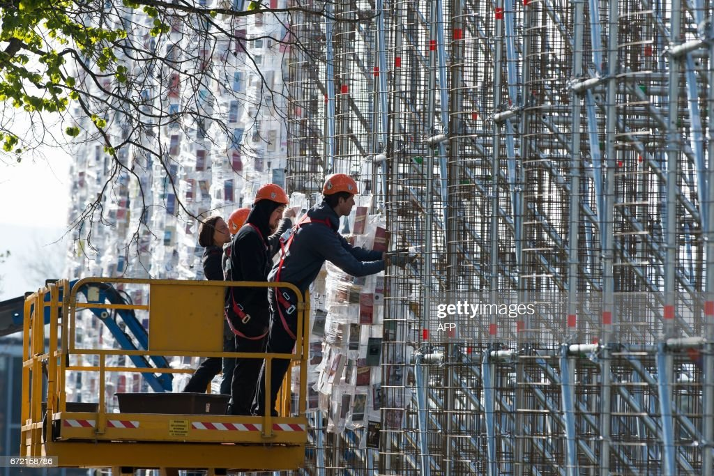 Workers fix books wrapped into plastic bags on a scaffolding