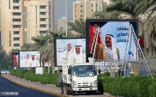 Workers fix large portraits of the emir of Kuwait, Sheikh Sabah al-Ahmad al-Jaber al-Sabah, on one of the main roads in Kuwait City on October 16 to...