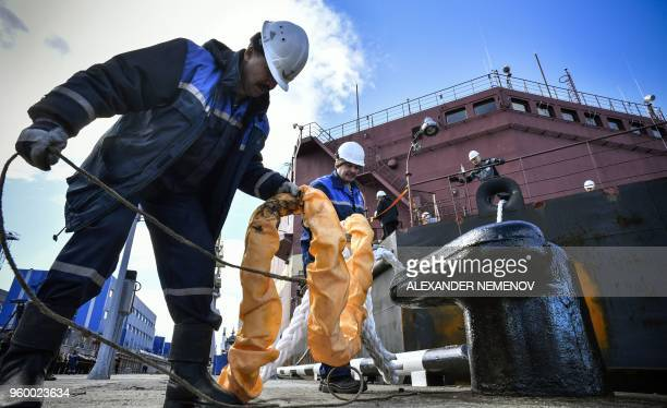 Workers fix mooring line of a floating power unit Akademik Lomonosov being towed to Atomflot moorage of the Russian northern port city of Murmansk on...