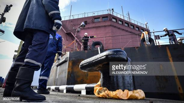 Workers fix mooring line of the floating power unit Akademik Lomonosov as it is towed to Atomflot moorage of the Russian northern port city of...
