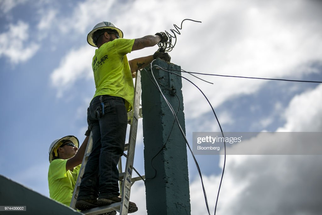 Workers fix power lines on the roof of a home in the town of Limones, Yabucoa, Puerto Rico, on Friday, May 18, 2018. The bankrupt U.S. commonwealth's investment bankers last week started sounding out suitors for the eight-decade-old monopoly known asPrepa, whose rickety infrastructure was almost erased by Hurricane Maria in 2017. The halting efforts to repair the damage and improve the antiquated grid have been the central obstacle in recovery. Photographer: Xavier Garcia/Bloomberg via Getty Images