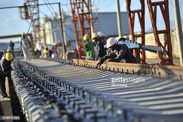 Workers fix steel rail track sections to concrete sleepers at the Kathekani Tgirder and rail sleeper manufacturing plant which makes parts for the...