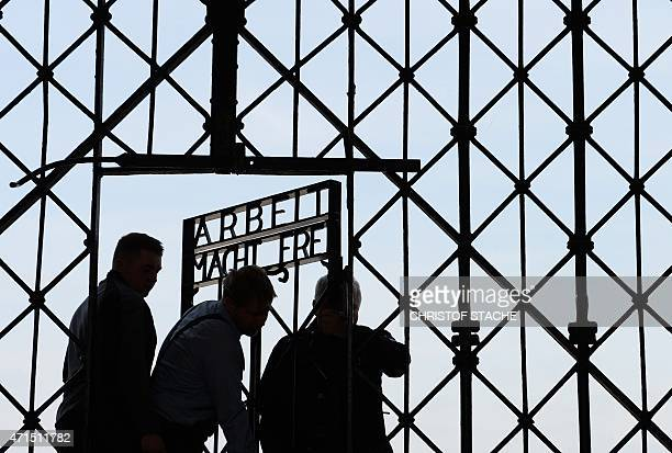 Workers fix the new entrance gate door with the inscription 'Work sets you free' of former concentration camp in Dachau southern Germany on April 29...