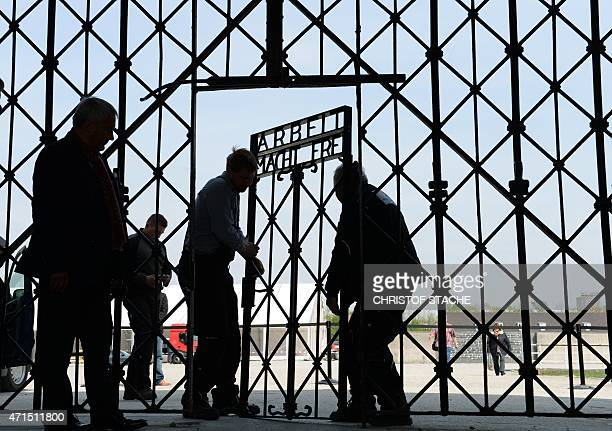 Workers fix the new entrance gate door with the inscription 'Work sets you free' of the former concentration camp in Dachau southern Germany on April...