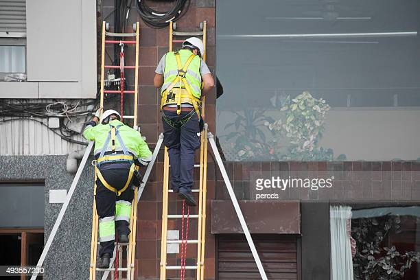 workers fixing telephone cables. - safety harness stock photos and pictures