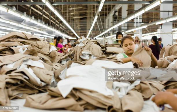 Workers folding clothing in garment factory