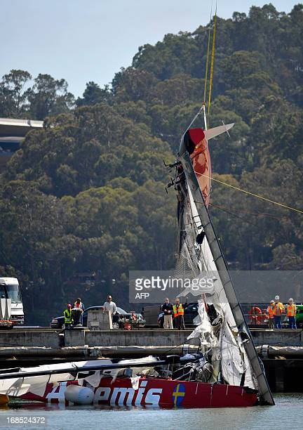 Workers for Artemis and America's Cup use a crane to lift the damaged Regata from the San Francisco Bay off the coast of Treasure Island in...