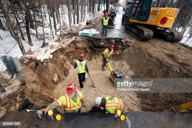Workers for Shaw Brothers Construction seal and bury a new section of water main on Windham Center Road at the bridge over Pleasant River on Thursday...