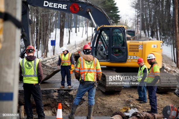 Workers for Shaw Brothers Construction watch for possible leaks as they restore water pressure to a new section of a water main on Windham Center...