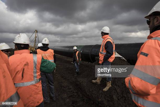 Workers for SpiecapagAktor JV watch as sideboom tractors lower a welded pipe section into a trench dug at the 685km point during the construction of...