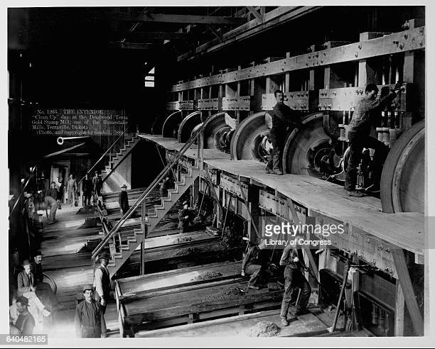 Workers for the Deadwood Terra Gold Stamp Mill a Homestake mill in Terraville Dakota clean the mill saws pulleys and platforms of their trade |...