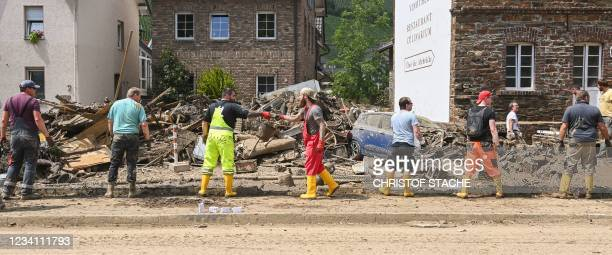 Workers form a human chain to remove debris in a muddy street of Dernau near Bad Neuenahr-Ahrweiler, western Germany, on July 22 days after heavy...