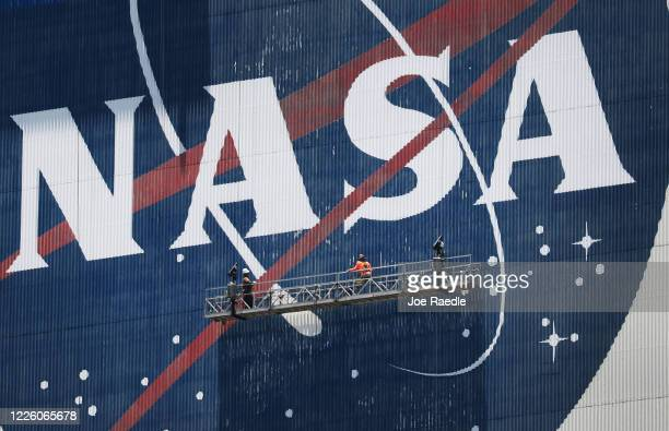 Workers freshen up the paint on the NASA logo on the Vehicle Assembly Building before the arrival of NASA astronauts Bob Behnken and Doug Hurley at...