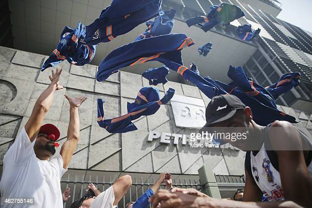 Workers from a company subcontracted by Brazil's governmentrun oil company Petrobras toss their work outfits into the air during a protest in front...