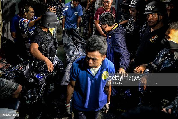 Workers from a funeral parlor escorted by armed guards carry out a corpse from the Paranaque city jail where a grenade blast killed 10 inmates 8 of...