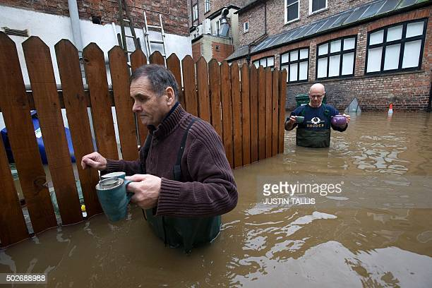 Workers from a taxi firm leave a neighbouring wine bar with a teapot and three cups of tea through the floodwaters from the rivers Foss and Ouse...