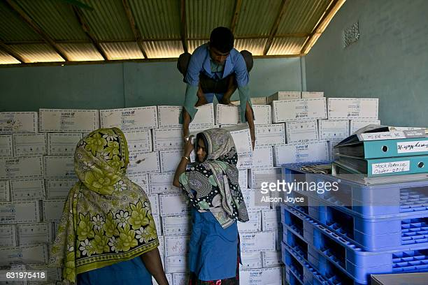 Workers from Action Contre La Faim in partnership with the World Food Program unload boxes of food at their center January 18 2017 in Coxs Bazar...