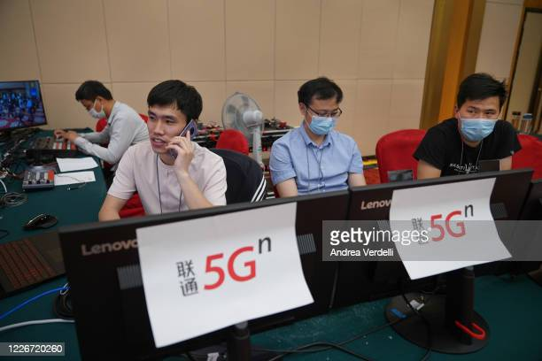 Workers from China Unicom, located at the Media Center with the press, supervise the equipment used to stream Chinese Foreign Minister Wang Yi video...
