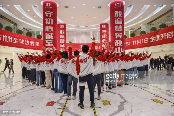 Workers from Chinese e-commerce giant JD.com pose for photos during a break for Singles Day in the lobby at the company's headquarters as part of an...