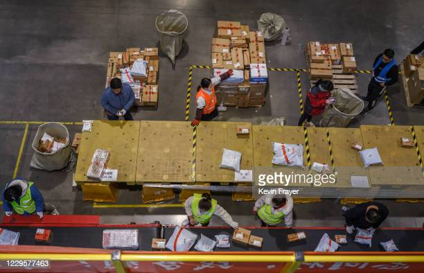 Workers from Chinese e-commerce giant JD.com prepare parcels for delivery at the company's main logistics hub during an organized tour for Singles...