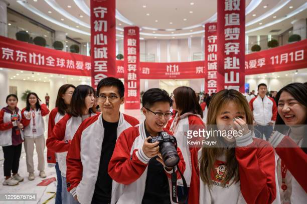 Workers from Chinese e-commerce giant JD.com react as they gather together for photos during a break for Singles Day in the lobby at the company's...
