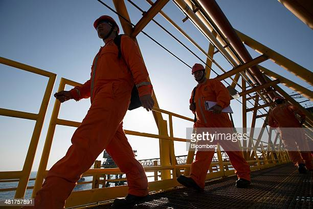 Workers from Cotemar SA an offshore oil field services company walk across a connecting bridge at the Petroleos Mexicanos PolA Platform complex...