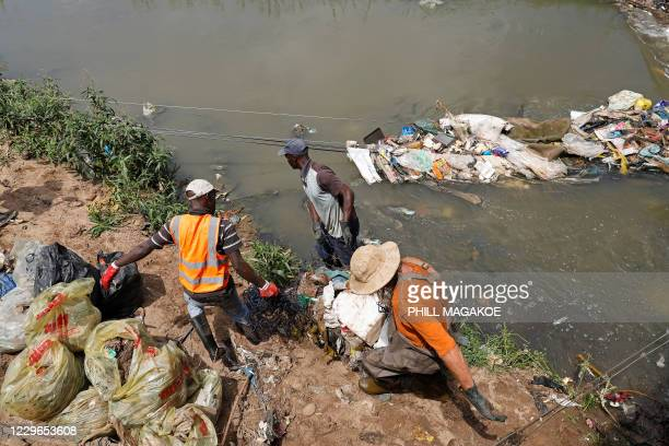 Workers from Freshngo carry plastic deluge removed from litter trap nets and long line cables that was washed down under a bridge on the Clayville...