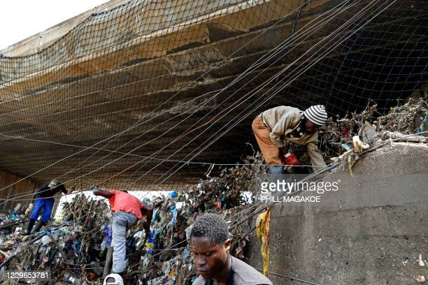 Workers from Freshngo remove plastic deluge from litter trap nets and long line cables that was washed down under a bridge on the Clayville tributary...