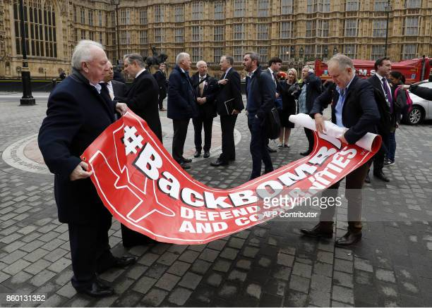 Workers from plane manufacturer Bombardier roll up a banner after a demonstration calling on the Government to help secure their jobs opposite the...